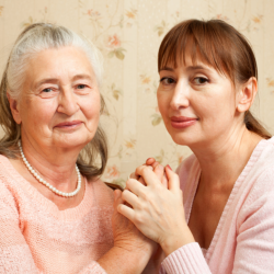 caregiver holding the hands of old patient